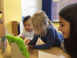 Das Bild zeigt Schulkinder, die mit einem Tablet lernen.