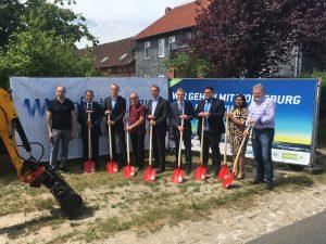 Das Bild zeigt Oberbürgermeister Klaus Mohrs sowie Vertreter der WOBCOM beim Spatenstich in Almke.